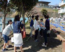 児童に案内されながらスマホを片手に校庭の様々な場所でスタンプラリーをする保護者