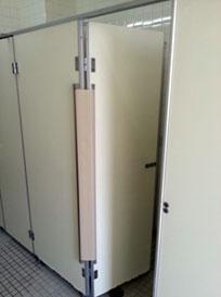 トイレ個室の吊元に取り付けられた「指はさまんぞう」が開閉に応じて隙間をガード