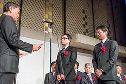 栗島聡JDMC会長より表彰状を授与される、同学 総合企画室 IR推進グループ 西出崇講師(中央)