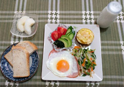 洋風献立「全粒粉パンのトースト、牛乳、ハムエッグ、野菜炒め、サラダ、ポテトのチーズ焼き、梨」