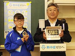 黒球付熱中症計を受けとる新井英和校長(右)と松崎里沙さん