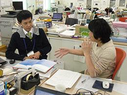 職員室で司書教諭と教員が打ち合わせ