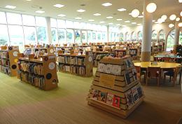 1Fの「こども図書館」。屋外には田園風景が広がっている。奥には「キッズルーム」と「おはなしのへや」があり、大型絵本などを配架している