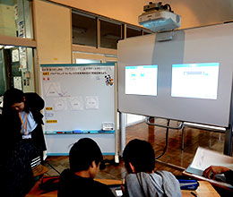 5年生4人はペアでプログラミングを考えた。互いの進捗状況は前方電子黒板でチラ見できる