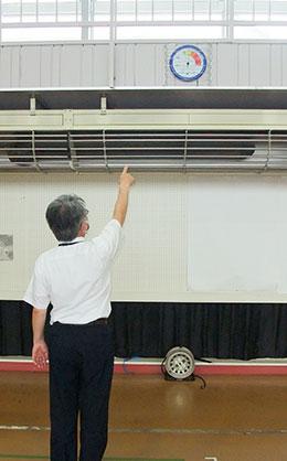 体育館の温湿度計を指さす佐久間副校長