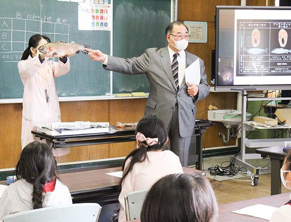 養殖場のニジマスを見せながら、尾びれの形状などの特徴を解説するニジマス博士(右)