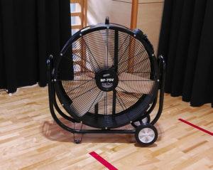 右側の格技場入り口から取り込んだ冷風を、2台のビックファンで室内全体に循環させている